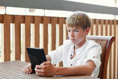 Serious teenager reading e-book — Stock Photo
