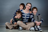 Portrait of happy mother and three sons, studio — Stock Photo