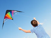 Boy flies kite into blue sky — Stok fotoğraf