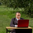 Man with red laptop working outdoors — Stock Photo #6741139