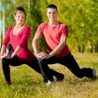 Man and woman woman doing yoga in park - Stock Photo