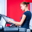 Young woman at the gym run on on a machine - 