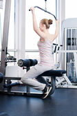 Kobieta robi rozciągające ćwiczenia na siłowni — Zdjęcie stockowe