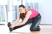 Woman doing stretching exercises at the gym — Stockfoto