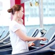 Young sporty woman run on machine — Stock Photo