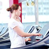 Young sporty woman run on machine — Stock Photo