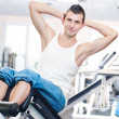 Stock Photo: Young mdoing exercises at gym