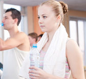 Man and woman drinking water after sports in gym — Stock Photo