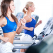 Two young women run on machine in the gym - Foto Stock