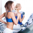 Two young women run on machine in the gym — Stock Photo #19935851