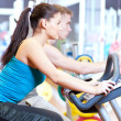 In the gym doing cardio cycling training - Stok fotoğraf
