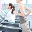 Woman and man at the gym exercising - ストック写真