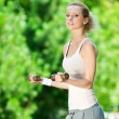 Woman doing dumbbell exercise outdoor - Foto Stock