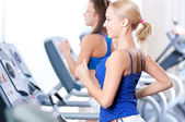Two young women run on machine in the gym — Stock Photo