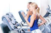 两名年轻妇女在健身房里的机器上运行 — 图库照片
