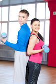 Man and woman at the gym doing stretching — Stock Photo
