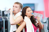 Man and woman drinking water after sports — Stock Photo