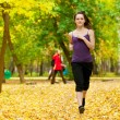 A young girl running in autumn park — Stock Photo #19942979