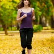 A young girl running in autumn park — Foto Stock