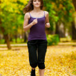 A young girl running in autumn park — Stok fotoğraf