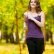 A young girl running in autumn park — Stock Photo #19943029