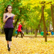 A young girl running in autumn park — Stock Photo #19943037