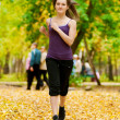 A young girl running in autumn park — Stock Photo