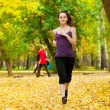 A young girl running in autumn park — Stock Photo #19943049