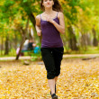 A young girl running in autumn park — Stock Photo #19943253