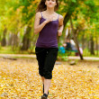 Royalty-Free Stock Photo: A young girl running in autumn park