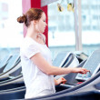 Young sporty woman run on machine - Stock Photo