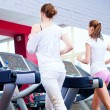 Two young sporty women run on machine - Stock Photo