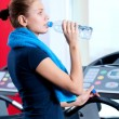 Woman at the gym drinking water — Stock Photo