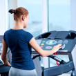 Young woman at the gym run on on a machine — Stock Photo