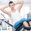 Young man doing exercises at gym - Stock Photo