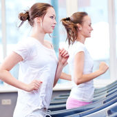 Two young sporty women run on machine — Stock Photo