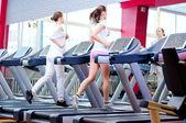 Two young sporty women run on machine — Stock Photo