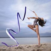 年轻的体操运动员的女孩舞蹈与功能区 — 图库照片