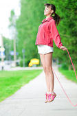 Teenage girl with skipping rope at park — Stock Photo