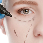 Beautician draw correction lines on woman face — Stock Photo