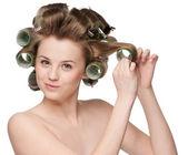 Mujer con rodillo de pelo que se encrespa — Foto de Stock
