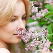 Stock Photo: Womwith lilac flower on face