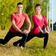 Man and woman woman doing yoga in park — Stock Photo #19961035