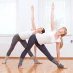 Women doing yoga exercise at gym — Stock Photo #19962961