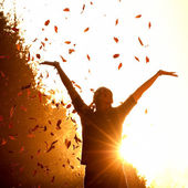 Sonbahar yaprakları ile oynayan kadın — Stok fotoğraf