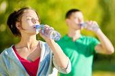 Homem e mulher beber da garrafa — Foto Stock