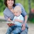 Stock Photo: Mother with son reading a book