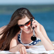 Woman talking by phone on a beach — Stockfoto