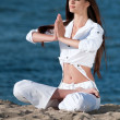 Woman practicing yoga on the beach - Photo