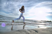 Sporty woman running in sea coast — Stock Photo